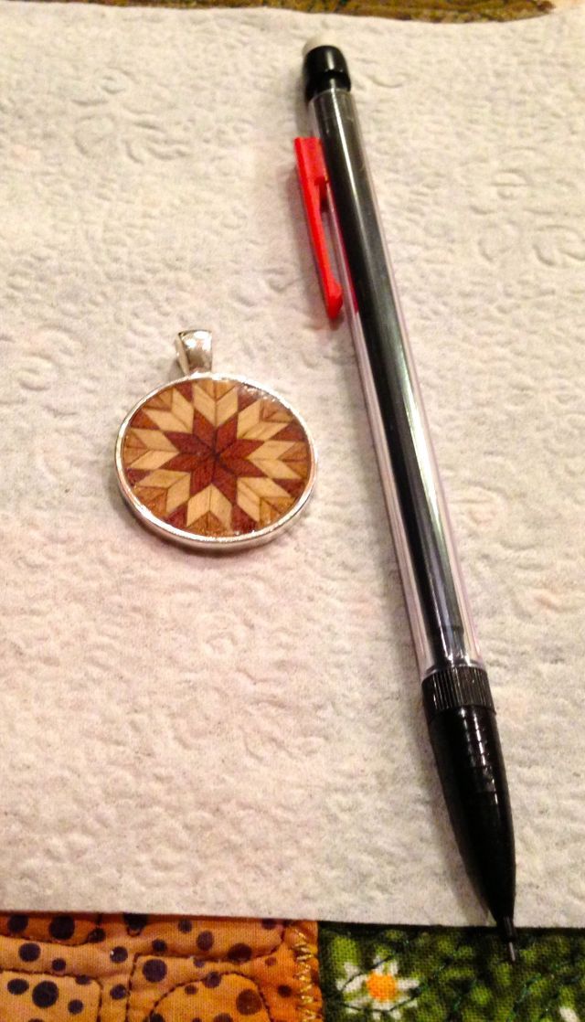 Parquetry set in a pendant bezel and sealed with polyester resin.